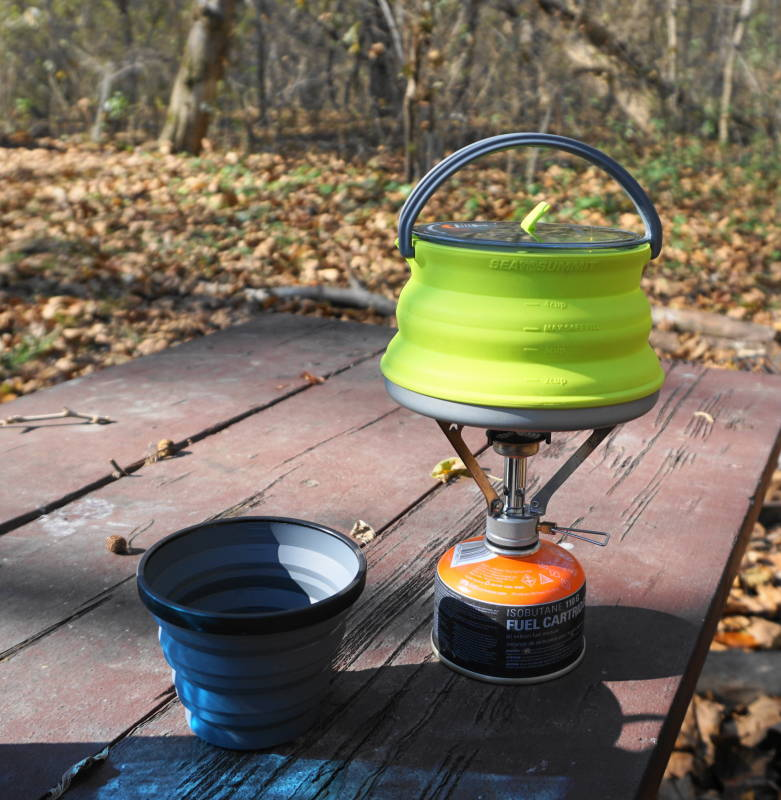 Lightweight camping stove with a SeaToSummit X-pot Kettle and X-cup on a picnic table.