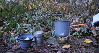 Picture of a small alcohol stove with a small pot on it heating water for tea with two cups, one a silicone collapsible backpacking cup and one a pewter tumbler.